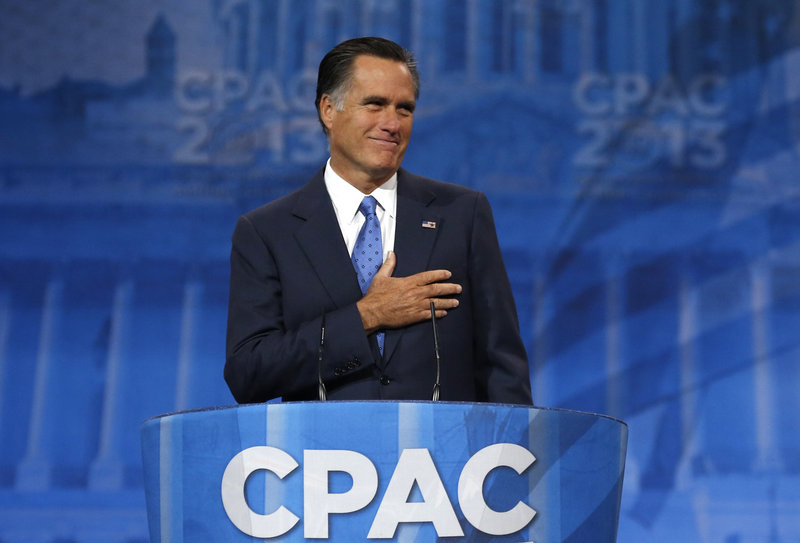 Former presidential candidate Mitt Romney puts his hand to his heart as supporters cheer him upon taking the stage at the Conservative Political Action Conference on Friday.