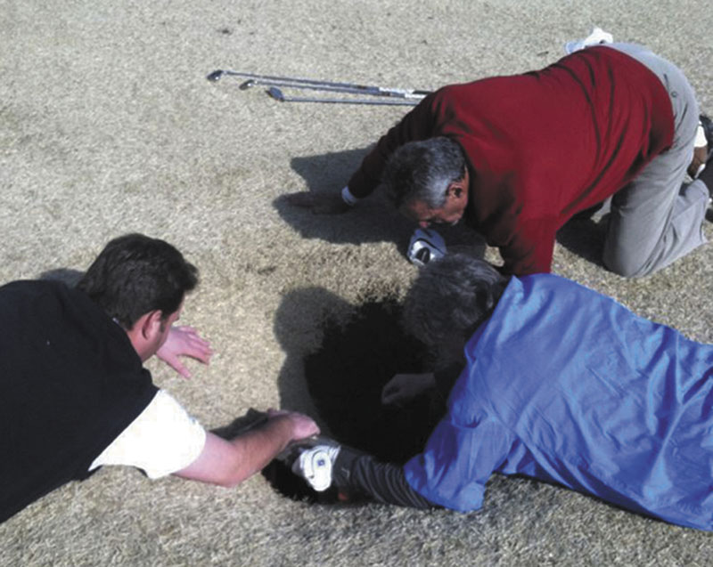 SINKHOLE: In this cell phone image taken Friday and provided by golfmanna.com, Hank Martinez, top, Ed Magaletta, right, and Russ Nobbe, look into an 18-foot-deep and 10-foot- wide sinkhole that golfer Mark Minhal fell into while playing golf at the Annbriar Golf Course in Waterloo, Ill. Mihal, 43, a mortgage broker from Creve Coeur, Mo., was hoisted to safety with a rope and suffered a dislocated shoulder.