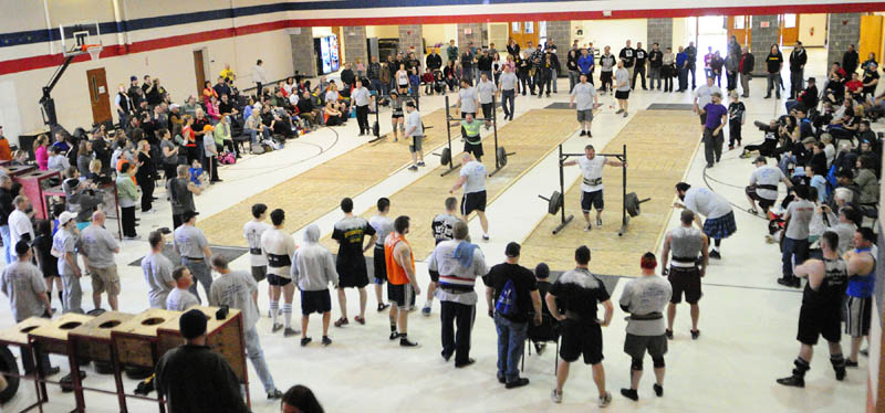 Three lanes of competitors walk carrying heavy loads, in the yoke walk event during the 2013 Central Maine Strongman contest on Saturday at the Augusta armory.