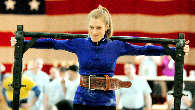 Annie Philbrick, of Sidney, carries a weighted yoke in the yoke walk event during the 2013 Central Maine Strongman contest on Saturday at the Augusta armory.