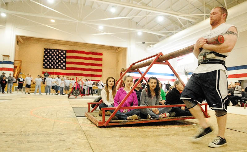 Brian Beaupain, of Waterville, carries several children around in a circle in the Conan's wheel event during the 2013 Central Maine Strongman contest on Saturday at the Augusta armory. Conan's wheel has contestants lifting and carrying a weight around a pivot. The contestant who carries it for the most laps wins.