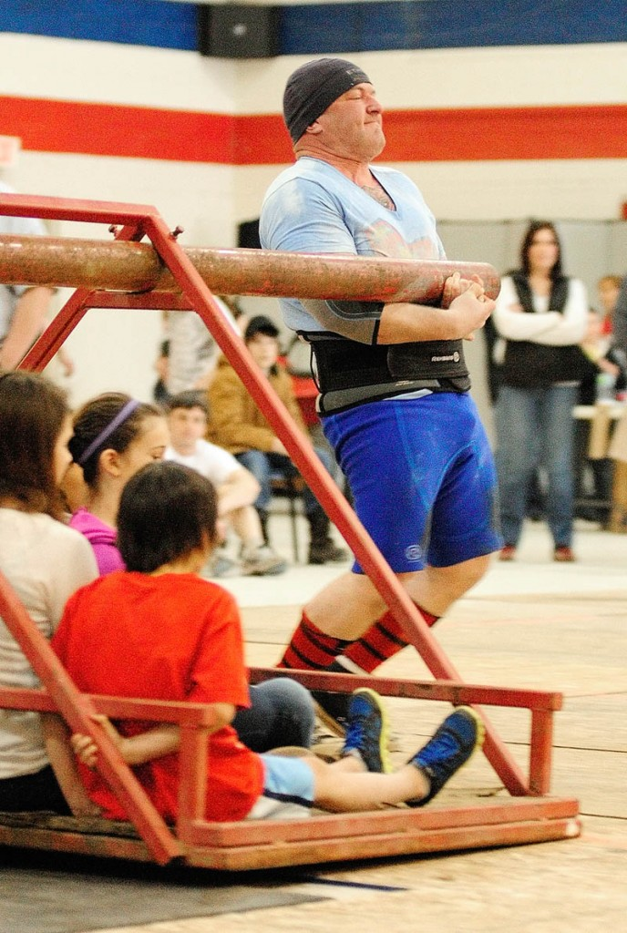 Rob Drummond, of Augusta, stops in exhaustion after carrying several children around a pivot in the Conan's wheel event, during the 2013 Central Maine Strongman contest on Saturday at the Augusta armory.