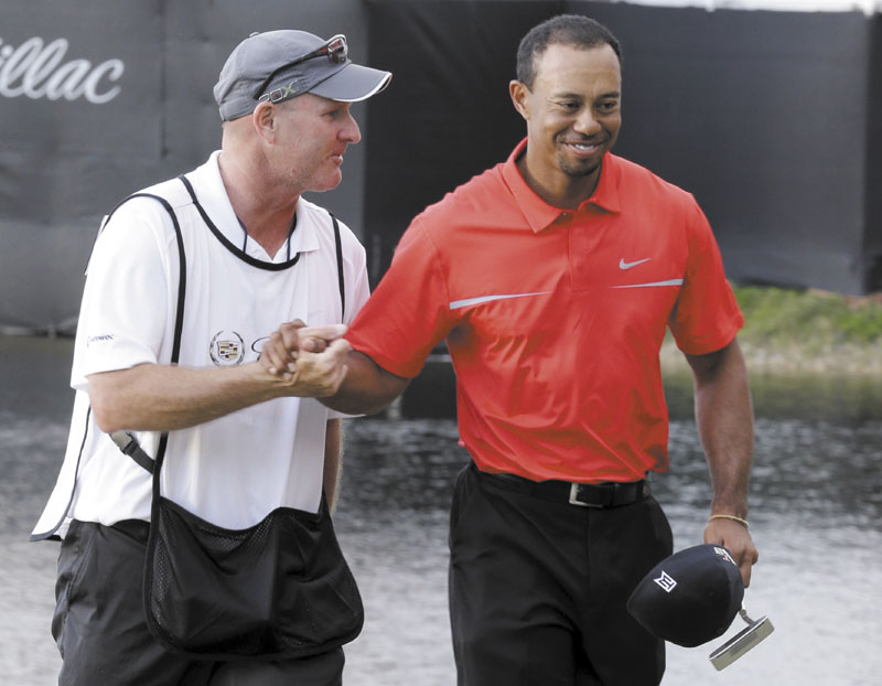 WAY TO GO: Tiger Woods, right, and his caddie Joe Lacava congratulate each other after Woods won the Cadillac Championship on Sunday, in Doral, Fla. WGC-Cadillac World Golf Champio
