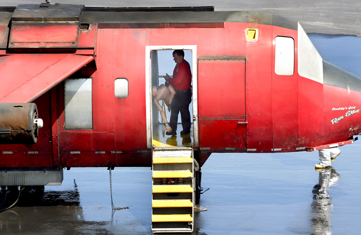 A firefighter positions a mannequin in the fuselage of an airplane for an training exercise at the Portland International Jetport on Tuesday. Part of the exercise involved firefighters rescuing mock passengers from the burning plane.