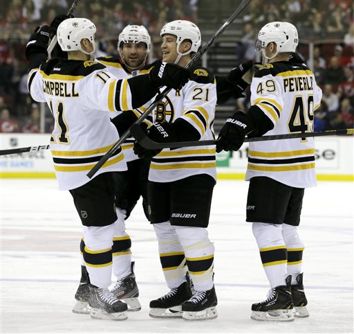 SCORING WAS CHANGED AFTER TRANSMISSION- UPDATES CREDIT OF THE GOAL FROM ANDREW FERENCE TO GREGORY CAMPBELL- Boston Bruins defenseman Andrew Ference (21) celebrates a goal by teammate Gregory Campbell, from left, with teammates Johnny Boychuk, Rich Peverley during the first period of an NHL hockey game against the New Jersey Devils, Wednesday, April 10, 2013, in Newark, N.J. (AP Photo/Julio Cortez)