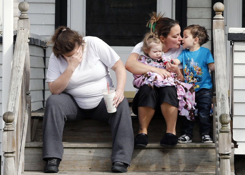 Neighbors sit outside the house of Krystle Campbell's parents in Medford, Mass.,Tuesday, April 16, 2013. Campbell was killed in Monday's explosions at the finish line of the Boston Marathon. (AP Photo/Michael Dwyer)