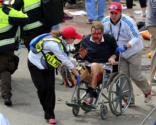 Medical workers aid an injured man at the 2013 Boston Marathon following the explosion in Boston on Monday.