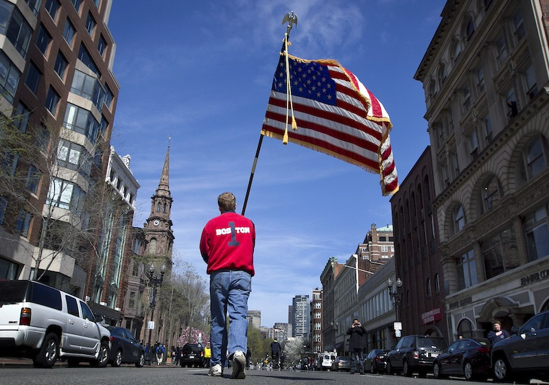 Lt. Mike Murphy of the Newton, Mass., fire dept., carries an American flag down the middle of Boylston Street after observing a moment of silence in honor of the victims of the bombing at the Boston Marathon near the race finish line, Monday, April 22, 2013, in Boston, Mass. At 2:50 p.m., exactly one week after the bombings, many bowed their heads and cried at the makeshift memorial on Boylston Street, three blocks from the site of the explosions, where bouquets of flowers, handwritten messages, and used running shoes were piled on the sidewalk. (AP Photo/Robert F. Bukaty)