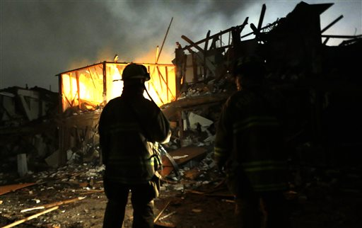 Firefighters use flashlights early Thursday morning to search a destroyed apartment complex near the fertilizer plant that exploded Wednesday night in West, Texas.