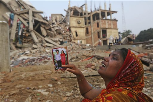 A Bangladeshi woman weeps as she holds a picture of herself and her missing husband while she waits near the site of the building collapse.