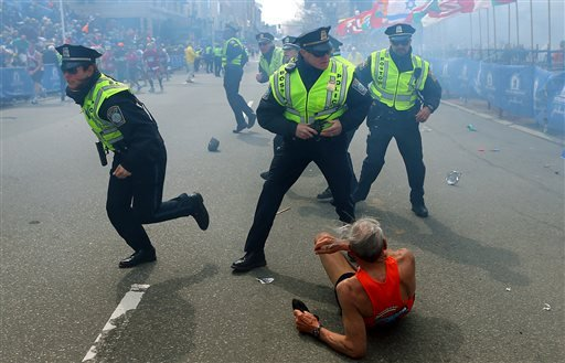 Bill Iffrig, 78, lies on the ground as police officers react to a second explosion at the finish line of the Boston Marathon in Boston on Monday. Iffrig, of Lake Stevens, Wash., was running his third Boston Marathon and near the finish line when he was knocked down by one of two bomb blasts.