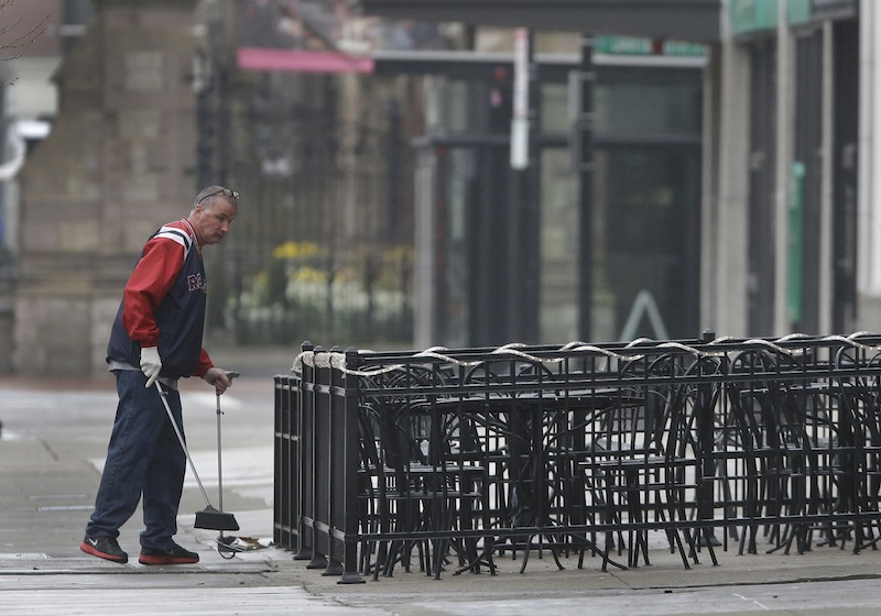 A man sweeps around the outdoor seating area at a business on Boylston Street in Boston Tuesday, April 23, 2013 about two blocks from the Boston Marathon finish line where two bombings killed three people and injured many. Boylston Street businesses near the finish area remain closed to the public, but business owners are slowly being allowed to prepare to re-open. (AP Photo/Elise Amendola)