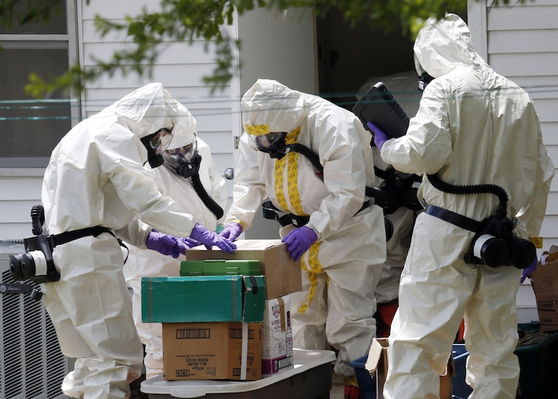Federal agents wearing hazardous material suits and breathing apparatus inspect the home and possessions in the West Hills Subdivision house of Paul Kevin Curtis in Corinth, Miss., Friday, April 19, 2013. The charges against Curtis were dropped Tuesday, April 23, 2013. (AP Photo/Rogelio V. Solis)