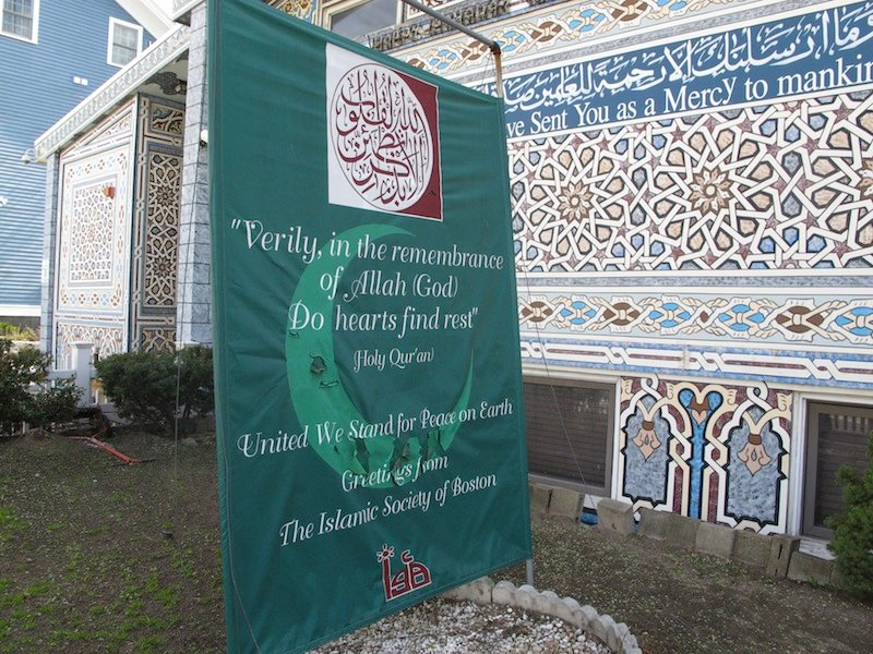 """A banner reading """"United We Stand For Peace on Earth"""" stands outside the Islamic Society of Boston mosque in Cambridge, Mass., on Friday, April 19, 2013. A mosque official confirmed that the two suspects in the Boston Marathon bombings, who lived a short distance away, worshipped there occasionally. Tamerlan Tsarnaev ranted at a neighbor about Islam and the United States. His younger brother, Dzhokhar, relished debating people on religion, """"then crushing their beliefs with facts."""" (AP Photo/Allen Breed)"""
