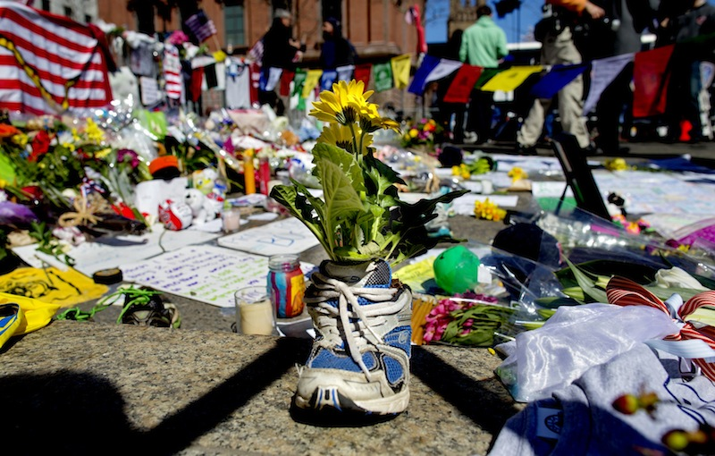 A memento of flowers in a running shoe rests at a makeshift memorial in Boston's Back Bay neighborhood on Thursday, April 18, 2013, a few blocks from the finish line of the Boston Marathon, where people continue to bring special objects to mourn and honor those who were killed and injured after two bombs exploded at the finish line of the race. (AP Photo/Craig Ruttle)