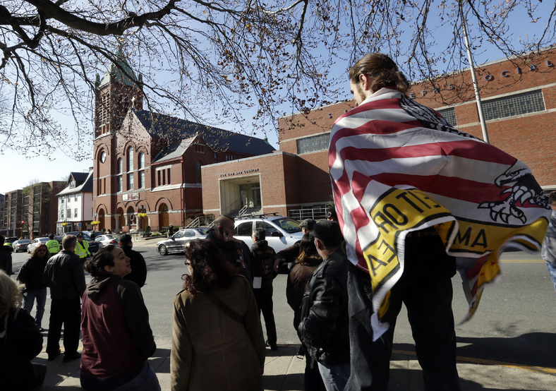 Devon Morancie of Littleton, Mass., wears a flag on his back as a crowd gathers outside the funeral for Boston Marathon bomb victim Krystle Campbell, 29, at St. Joseph's Church in Medford, Mass., on Monday.