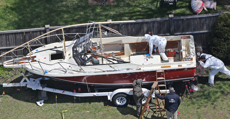 Investigators from the FBI inspect the boat where Boston Marathon bombing suspect Dzhokhar Tsarnaev was found hiding Friday night in a backyard in Watertown, Mass. Bullet holes are visible in the hull.