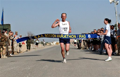 "FILE - In this April 15, 2006 file photo released by the U.S. Air Force, Navy Lt. Cmdr. Matt Simms crosses the finish line to win the 2nd Annual Boston Marathon/Iraq in Ali Base, Talil, Iraq. Lt. Col. Rodney Freeman is being honored by the Boston Athletic Association prior to the April 2013 Boston Marathon, with its Patriots Award for his work in establishing the ""shadow marathon"" at his military base in Iraq. (AP Photo/Master Sgt. Jon Hanson, U.S. Air Force, File)"