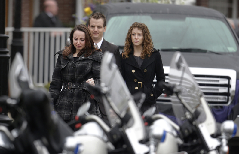 Mourners walk past police motorcycles as they depart St. Patrick's Church in Stoneham, Mass., following a funeral Mass for Massachusetts Institute of Technology police officer Sean Collier, on Tuesday. Collier was fatally shot on the MIT campus on Thursday, allegedly by the Boston Marathon bombing suspects.