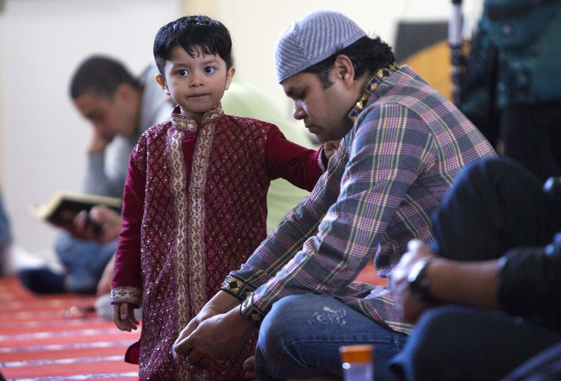 A boy stands next to his father during a prayer service at the Islamic Society of Boston mosque in Cambridge, Mass., on Friday.