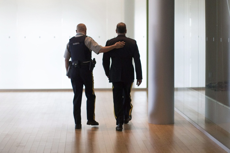 A Royal Canadian Mounted Police officer pats a colleague on the back before a news conference in Toronto as the RCMP announce the arrest of two men accused of plotting a terror attack on a passenger train on Monday.