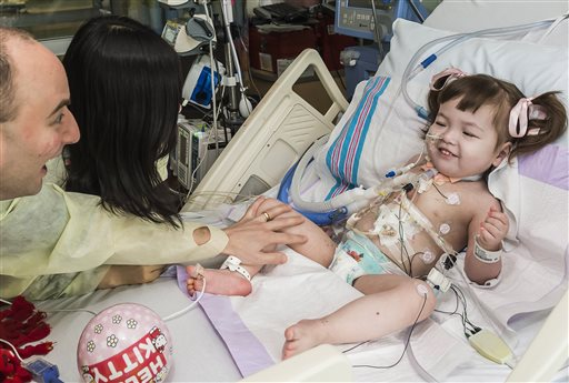 Darryl Warren and Lee Young-mi visit their 2-year-old daughter, Hannah Warren, in a post-op room at the Children's Hospital of Illinois in Peoria after she received a new windpipe. She is the youngest patient ever to get the experimental treatment.
