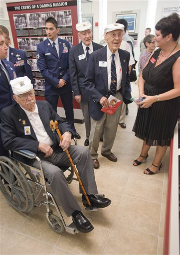 Doolittle Raiders, in white caps, left to right, Edward J. Saylor, David J. Thatcher and Richard E. Cole view the new Doolittle Raiders exhibit at Northwest Florida State College in Niceville, Fla.