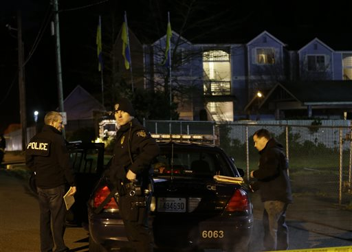 Police officers stand by their car on Monday morning at the scene of an overnight shooting that left five people dead at the Pinewood Village apartment complex in Federal Way, Wash.