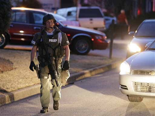 A police officer leaves the scene after an explosion and gunshots were heard where a man was holding four firefighters hostage on Wednesday in Suwanee, Ga.