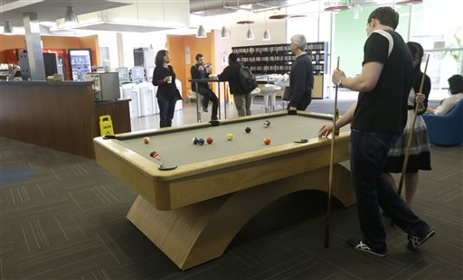 Google employees shoot pool at in a break room at the Google campus in Mountain View, Calif., recently. Companies say extraordinary campuses are a necessity, to recruit and retain top talent, and to spark innovation and creativity in the workplace.