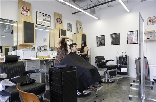 Facebook employee Noah Singer gets his hair cut by Charlotte Schaetzle at Johnny D's Barber Shop on the Facebook campus in Menlo Park, Calif.