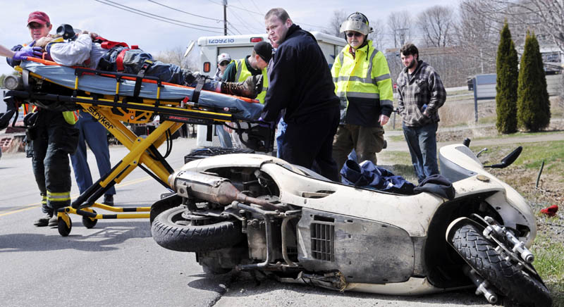 Firefighters carry the victim of a mo-ped accident Tuesday on the Hallowell Road in Chelsea. State police are investigating the wreck, which injured the driver.