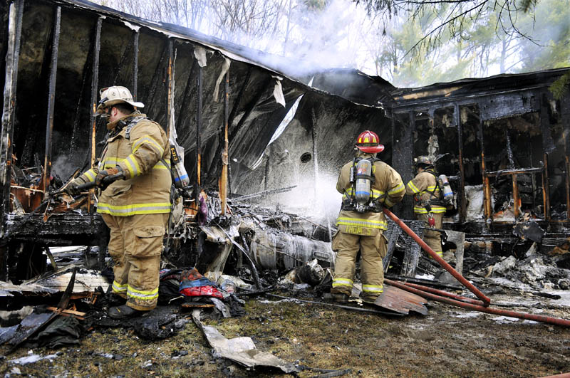 Firefighters extinguish a fire that destroyed a home in Monmouth Monday. Firefighters from several communities arrived at the residence Back Street to discover fire emerging from every corner. No injuries were reported, according to firefighters.