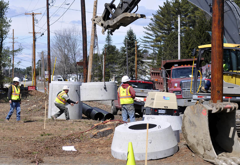 Contractors set up drainage culverts on Old Belgrade Road, near Civic Center Drive in Augusta, on Monday. The work is part of a nearly $13 million project to connect routes 3 and 27 and allow Interstate 95's exit 113 to function in all directions.