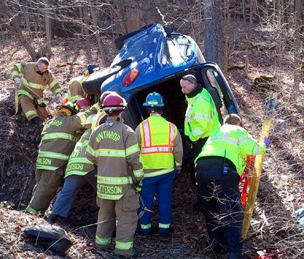 Rescue crews work to get Christina Poulin, 22, of Augusta out of her overturned PT Cruiser Wednesday morning after police said she swerved to avoid a turning car and went over an embankment.
