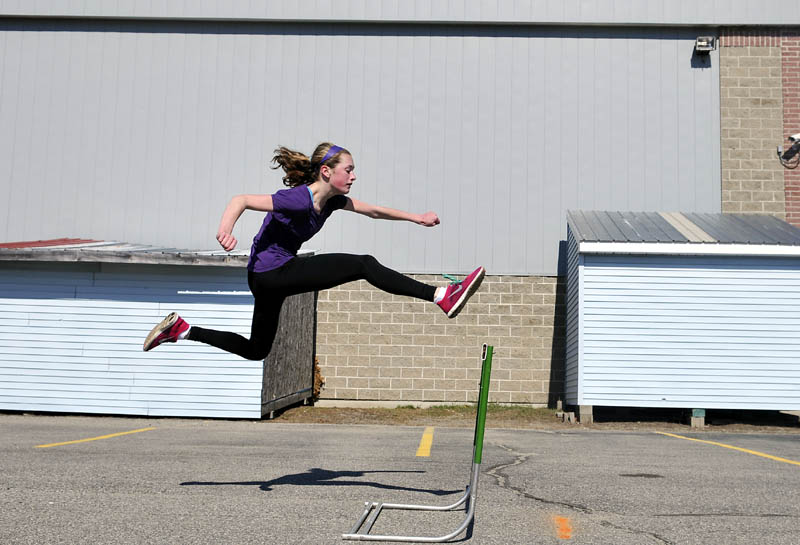 Sammy Grandahl, 15, leaps a hurdle Monday during track practice in the parking lot of Monmouth Academy. The school's athletes have already competed in one meet, coach Norm Thombs said, and are conditioning for several more, even though the school does not have a track to practice upon.