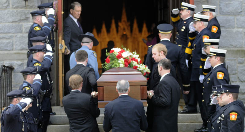 Gardiner police, left, and firefighters salute as the remains of William MacDonald are carried into funeral services Tuesday at St. Joseph's Catholic Church in Gardiner. MacDonald was Gardiner's commissioner of public safety, a joint of position of police and fire chief, from 1959 to 1979, then was elected mayor in the early 1980s. MacDonald died Wednesday in Gardiner, where he was born 88 years ago. He is survived by his wife of 60 years, Christine MacDonald, and several generations of children and grandchildren.