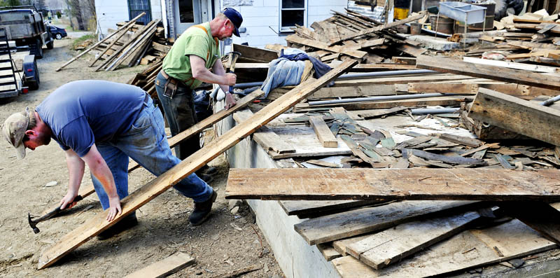 """Patrick, left, and Harlan Prescott on Sunday pound nails out of boards pulled from a barn they are taking apart at the former Quimby dairy farm in Augusta. Father and son started disassembling the three story hay barn built in 1920 in mid-March and plan to sell the wood recovered from the structure. """"We salvage everything, including the nails,"""" Harlan Prescott said."""