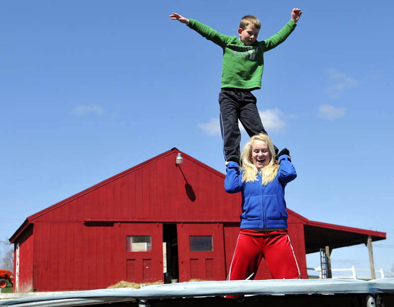 Anna Kulinski, 14, lets go of her brother, Jason, 9, while practicing acrobatics Sunday on the trampoline behind their Monmouth farmhouse. The siblings were practicing flips and landings that the elder Kulinski performs on the Monmouth Academy cheering squad.