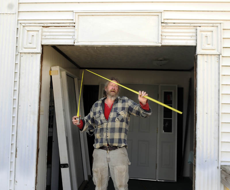 Frank Smith of New Sharon Monday measures the opening for new doors he planned to hang at the entrance of the Vienna Baptist Church. Organized in 1820 and erected in 1840, the church has served the community for over 150 years.