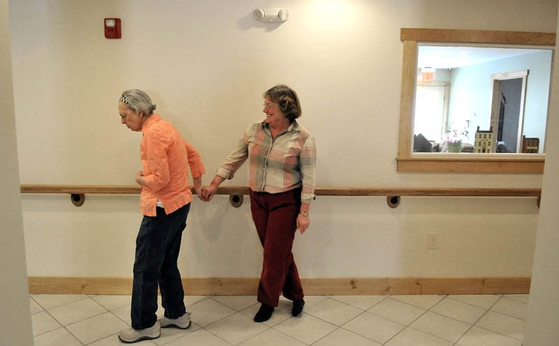 June Meres, left, grabs the hand of visitor Christine Pillsbury, as Meres roams the halls at Bedside Manor on Belgrade Road in Oakland on Wednesday.