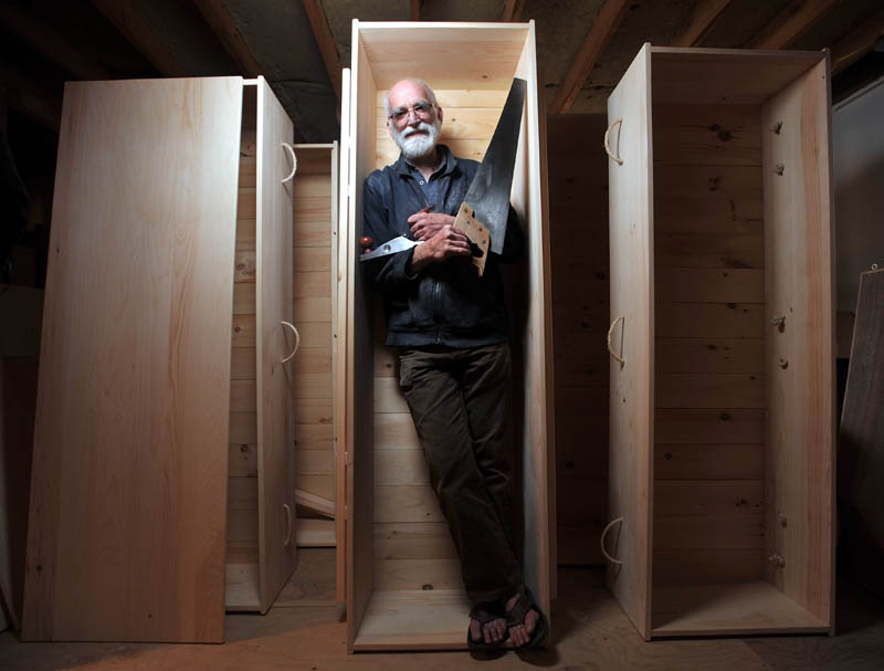 Chuck Lakin, 67, stands inside one of his handmade coffins in his workshop, in the basement of his Waterville residence, on Saturday.