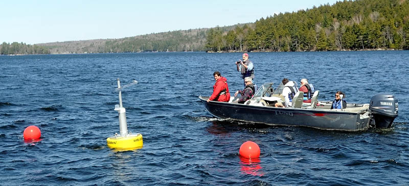Colby College and Belgrade Regional Conservation Alliance researchers float past the research buoy named Goldie on Great Pond in Belgrade Thursday. The research buoy can be accessed online to inspect data it collects.