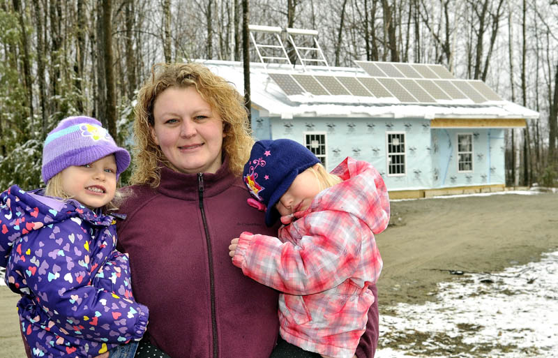 Joni Sprague and her twin, 3-year old daughters, Allie, left, and Kylie, in front of their Habitat for Humanity home,outfitted with solar panels, on Jacques Lane in Oakland on Saturday. The family will be moving in to their home in June.