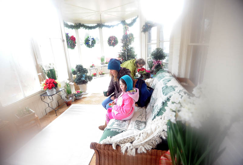 Mia Lambert, 6, of Kingfield, sits with her friend, Eileen McGuire, on the sun porch of the Octagon House in downtown Farmington Saturday. The Farmington Historical Society recently opened the home for tours.