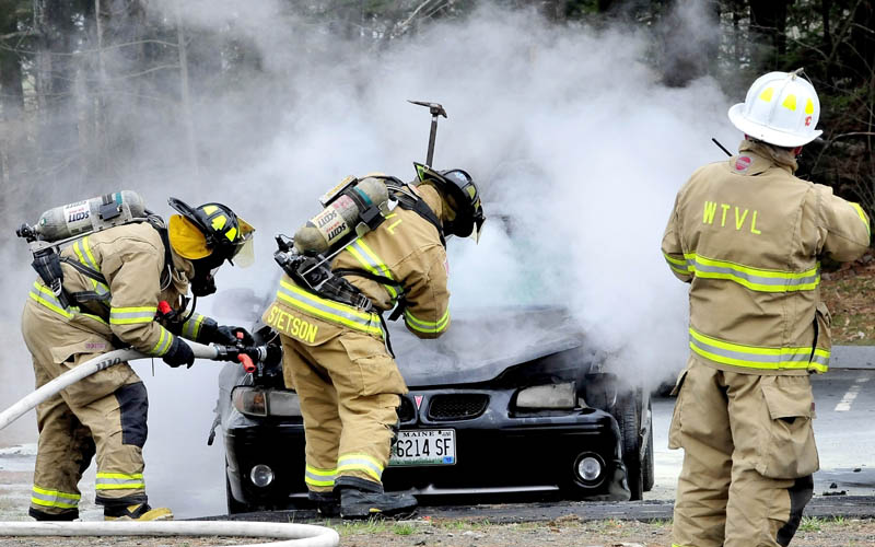 A Waterville firefighter sprays water on a burning vehicle while another firefighter uses an axe to raise the hood of the car parked at Thomas College in Waterville on Wednesday.