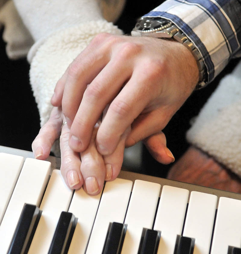 "Scott McManaman gently helps Martha Fabian play ""Chopsticks"" on the keyboard, at Bedside Manor on Belgrade Road in Oakland on Wednesday."