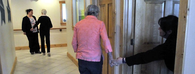June Meres, left center, an Alzheimer's patient at Bedside Manor, tries to pull Julie Benecke, right, from her office for a walk around the facility on Belgrade Road in Oakland on Wednesday. In the background, Martha Fabian, also a resident of Bedside Manor, walks the halls with care attendant Maribeth Beland.