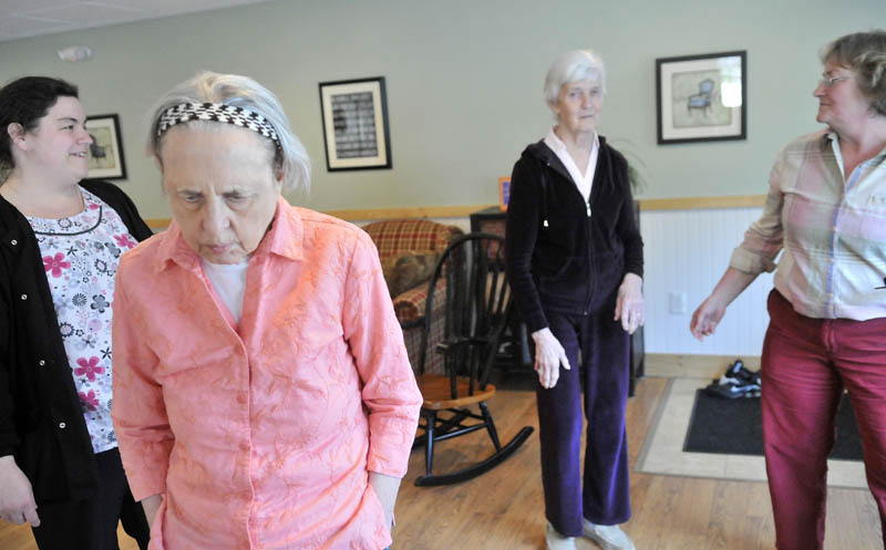 June Meres, left center, and Martha Fabian, right center, both Alzheimer's patients at Bedside Manor on Belgrade Road in Oakland, visit with Christine Pillsbury, far right, under the supervision of care attendant Maribeth Beland, far left, on Wednesday.