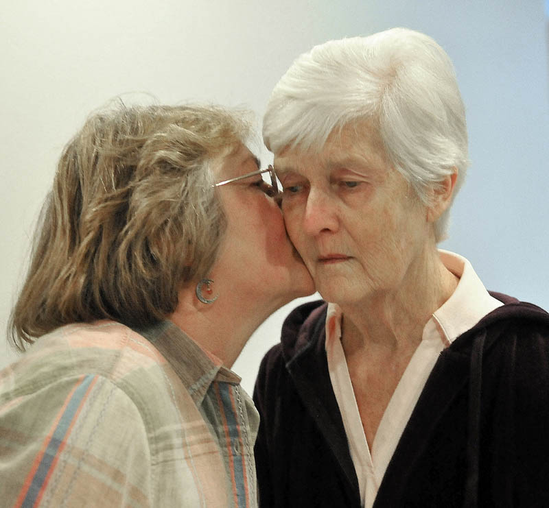 Christine Pillsbury, left, gives her friend, Martha Fabian, a kiss on the cheek after a visit at Bedside Manor on Belgrade Road in Oakland on Wednesday.